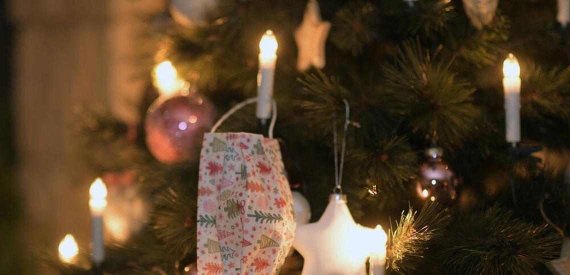 Maske hängt an beleuchtetem Weihnachtsbaum