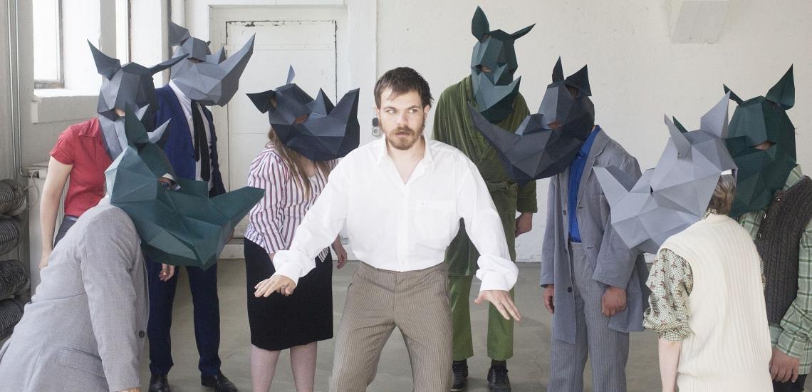 Mann wird von als Nashörnern kostümierten Schauspielern umzingelt