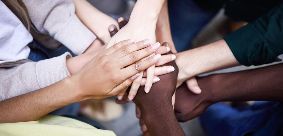 Jugendliche unterschiedlicher Hautfarbe halten Hände übereinander