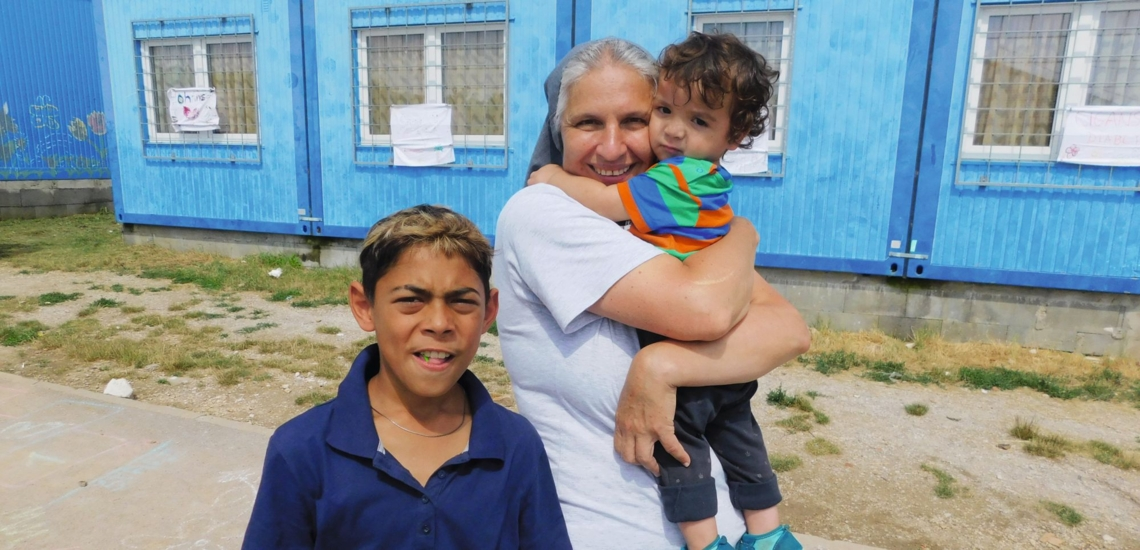 Schwester mit zwei Kindern vor Container