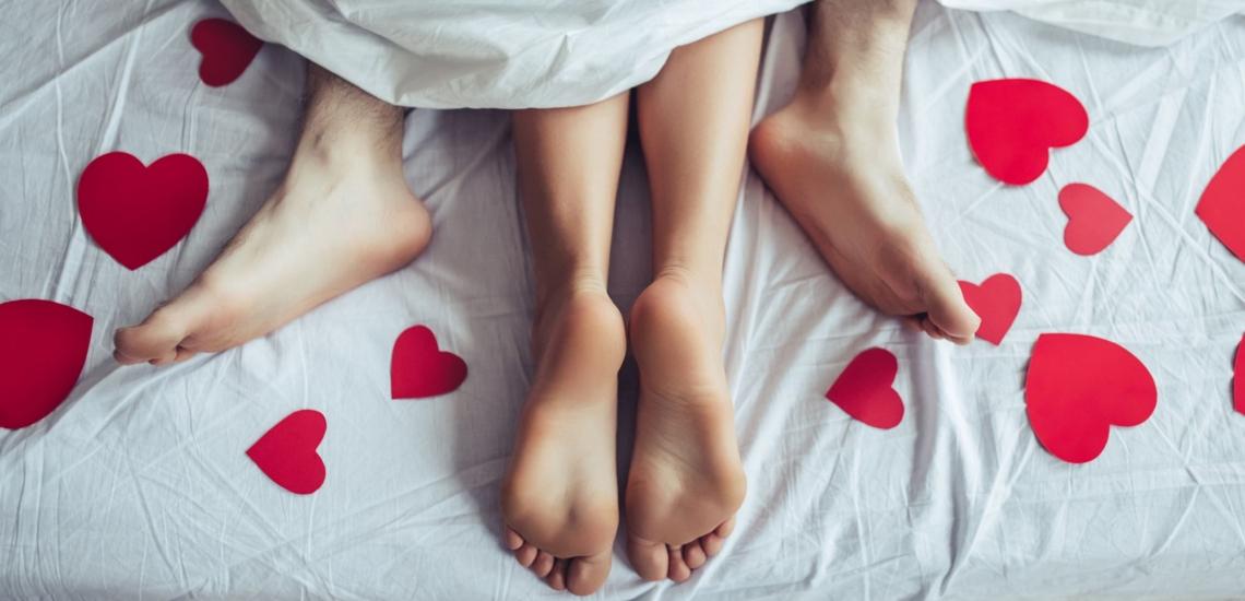 Füße von Paar im Bett beim Sex mit roten Herzen