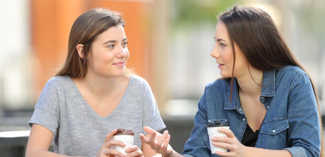 zwei Schwestern unterhalten sich draußen und trinken Kaffee