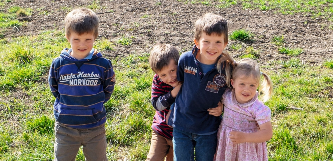 Vier Kinder auf Rasen