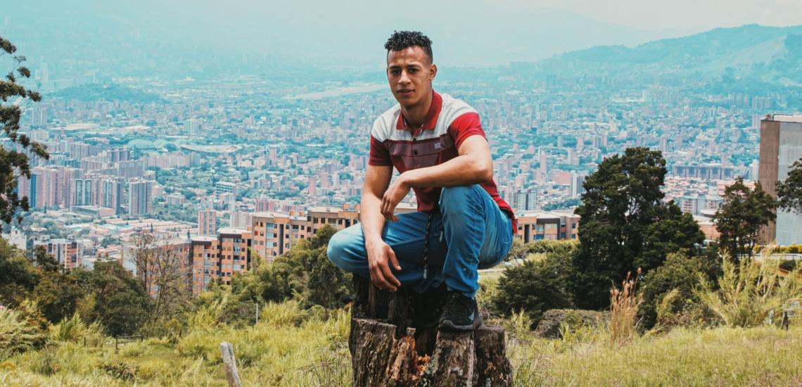 Junger Mann vor Stadtkulisse