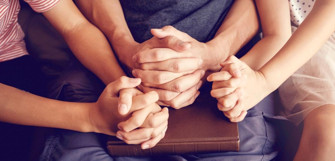 Hände von Erwachsenem und Kindern in Gebetshaltung