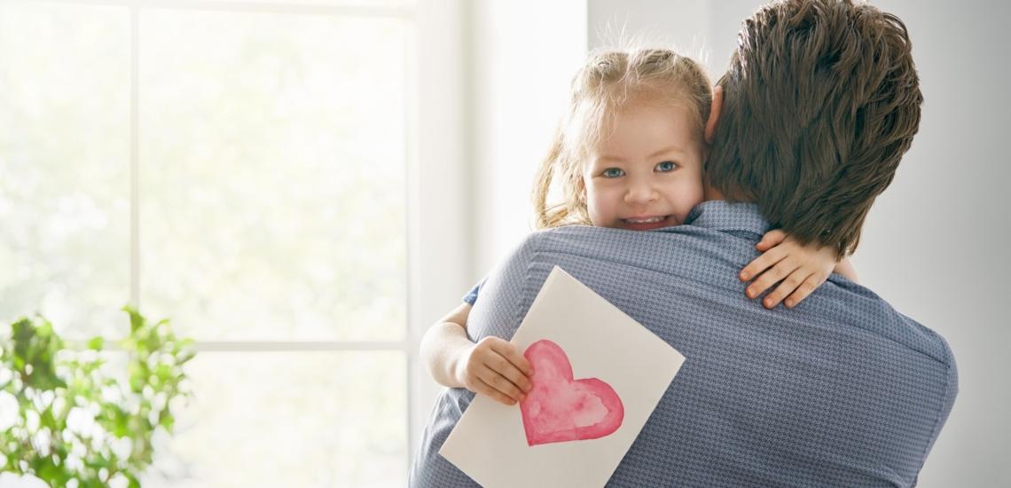 Tochter auf Arm von Vater hält Blatt mit rotem Herz in der Hand