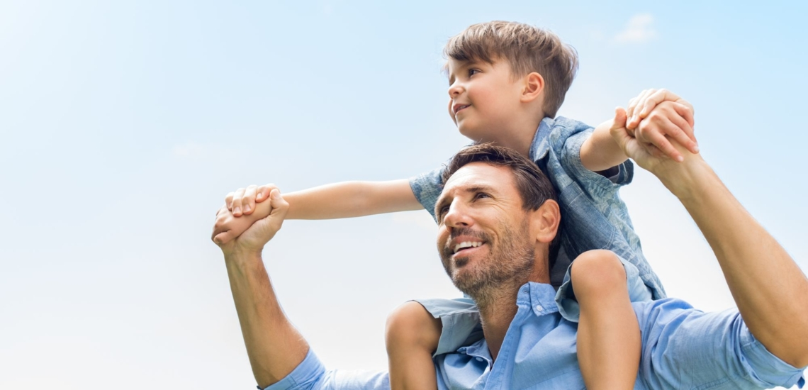 Vater froh mit Sohn auf seinen Schultern