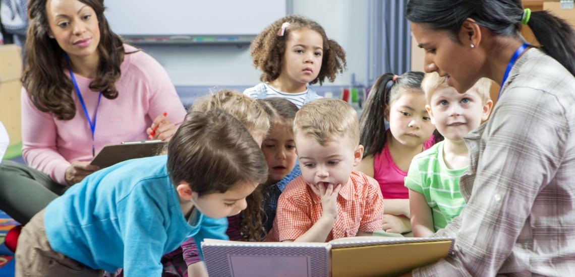 Kindergartenkinder lesen Buch mit Erzieherinnen