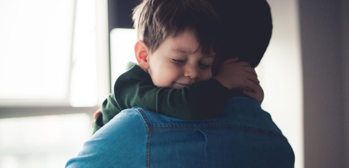 Kind geborgen auf dem Arm des Vaters