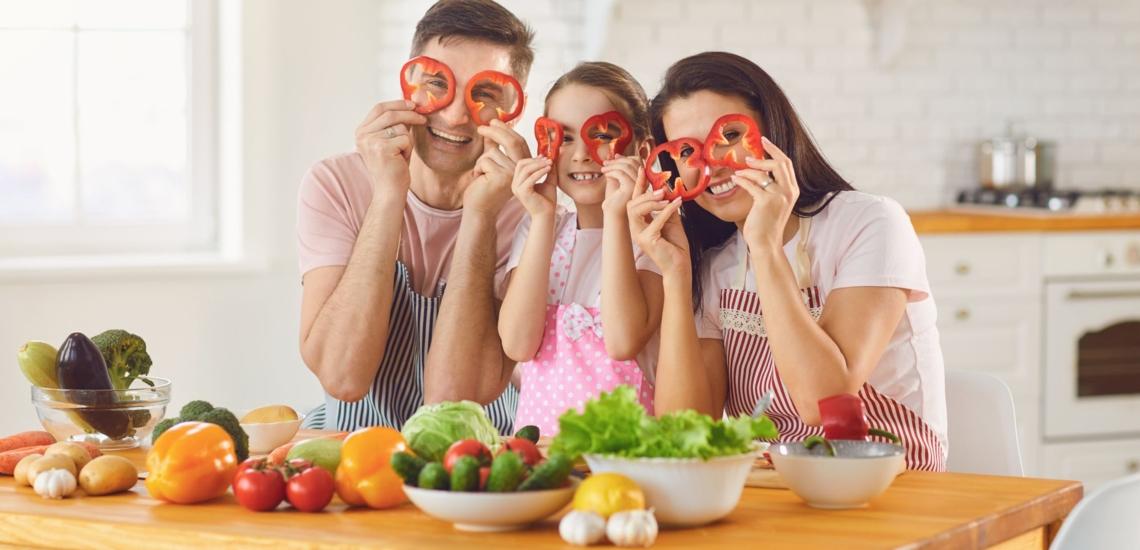 Eltern und Kind halten sich Paprikaringe vors Gesicht