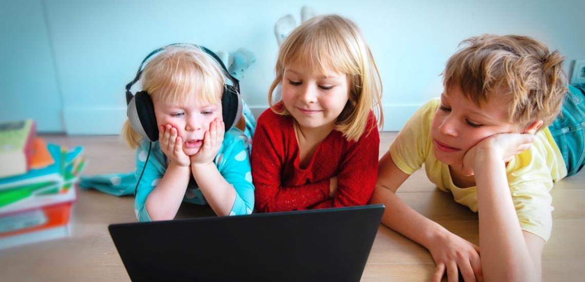 drei Kinder liegen auf Boden und schauen auf Notebook