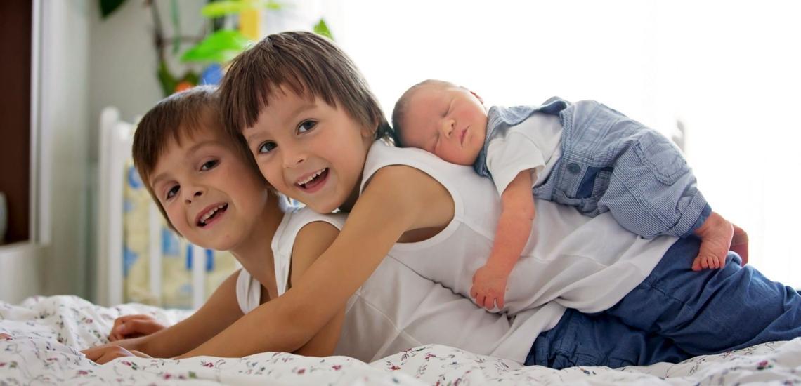 Drei Geschwister liegen übereinander auf dem Bett