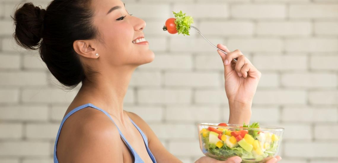Jugendliche isst genüsslich Salat