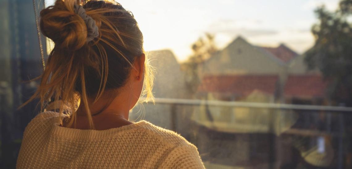 Frau von hinten schaut aus Fenster