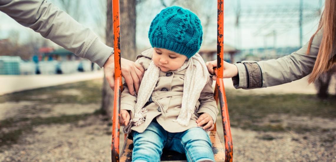 Kind auf Schaukel zwischen Eltern