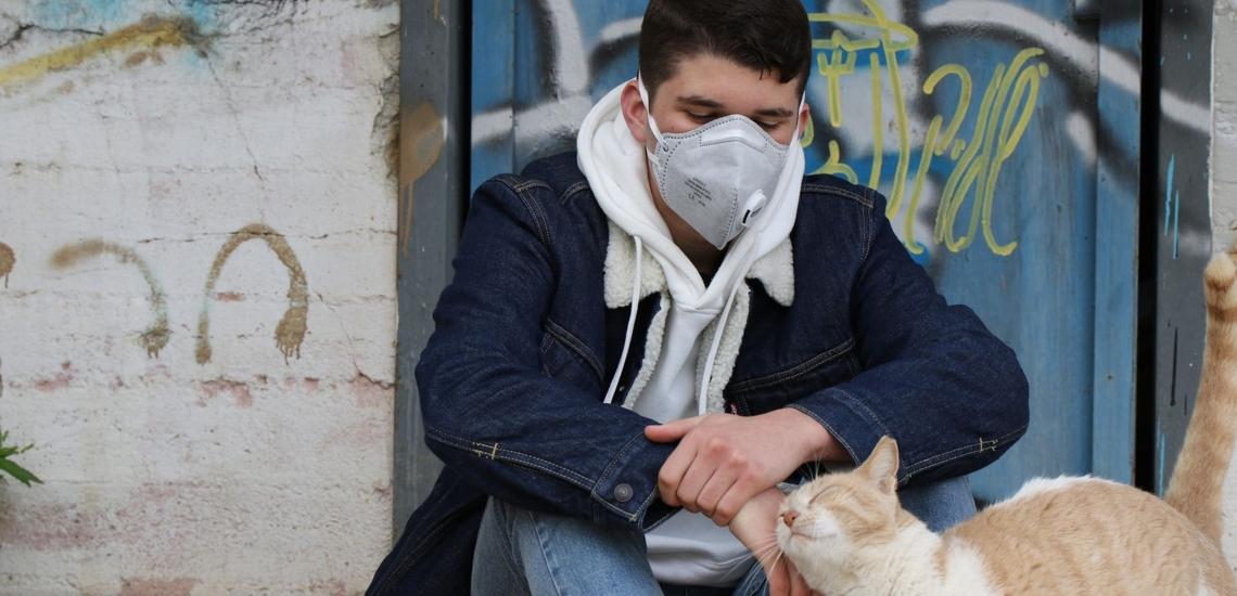 Jugendlicher mit Maske streichelt Katze