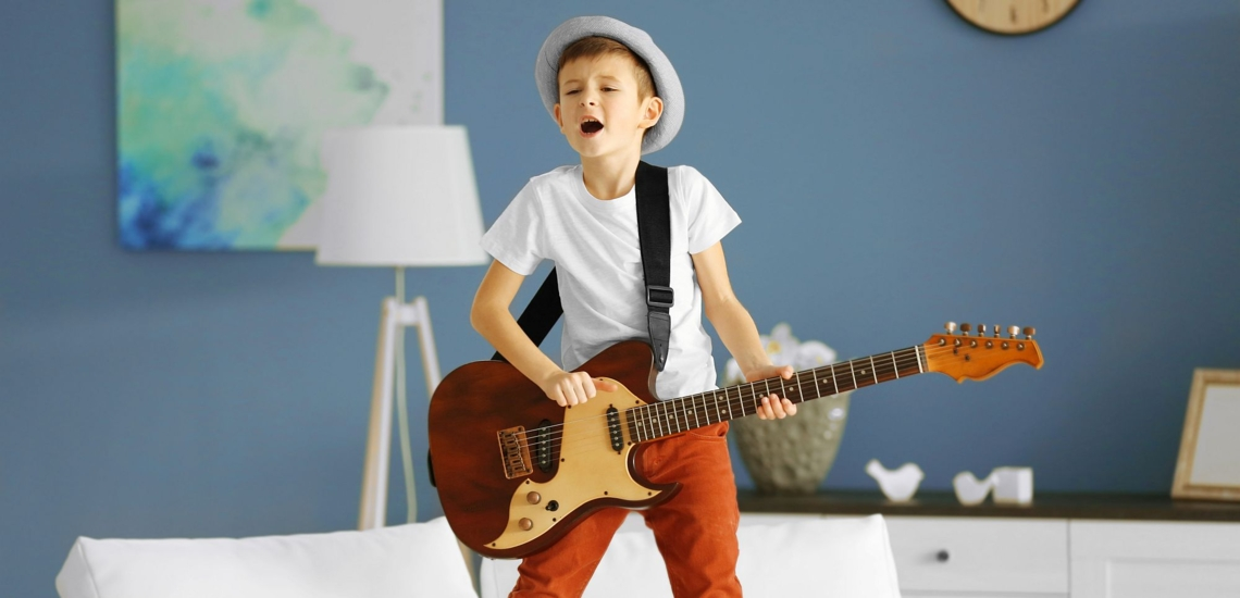 Junge singend mit E-Gitarre im Wohnzimmer