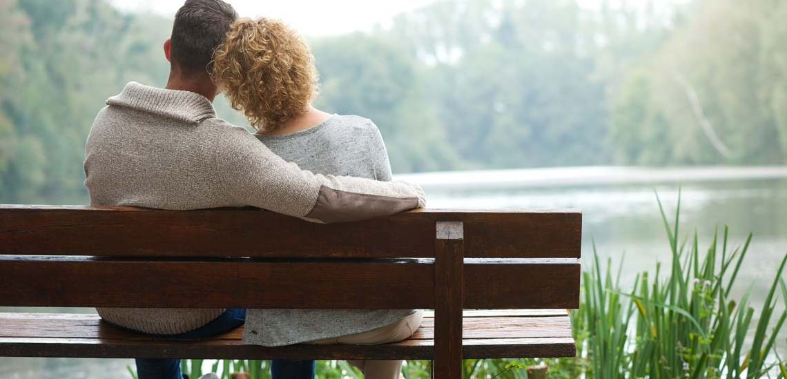 Rückenansicht Paar nachdenklich aneinander gelehnt auf Bank