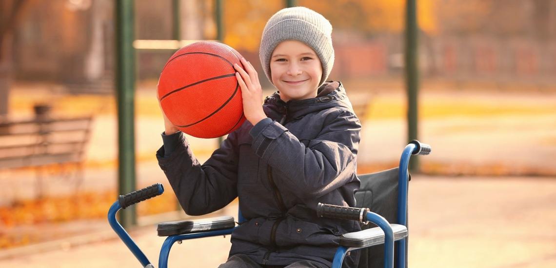 Junge im Rollstuhl hält Basketball