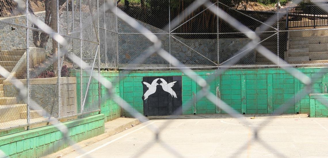 Sportplatz mit Bild von Friedenstauben auf einer Mauer