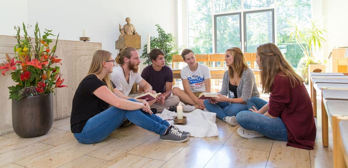 Jugendliche sprechen im Kreis auf dem Boden in der Kapelle des Münchner Salesianums