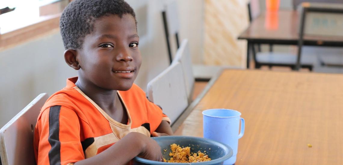 Junge bei Don Bosco in Ghana sitzt am Tisch und isst
