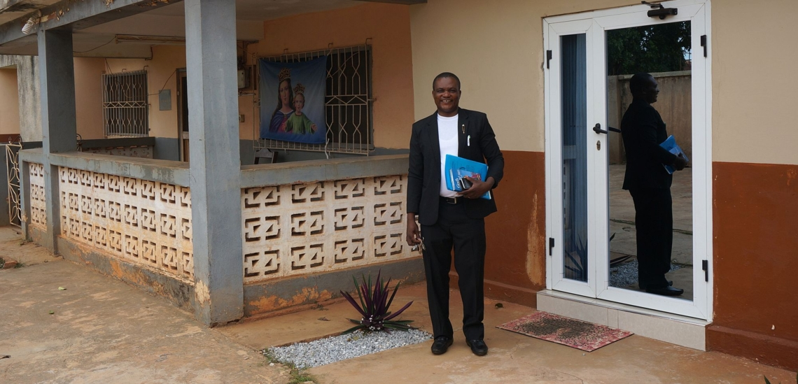 Pater Robertson Sung vor Haus in Ghana