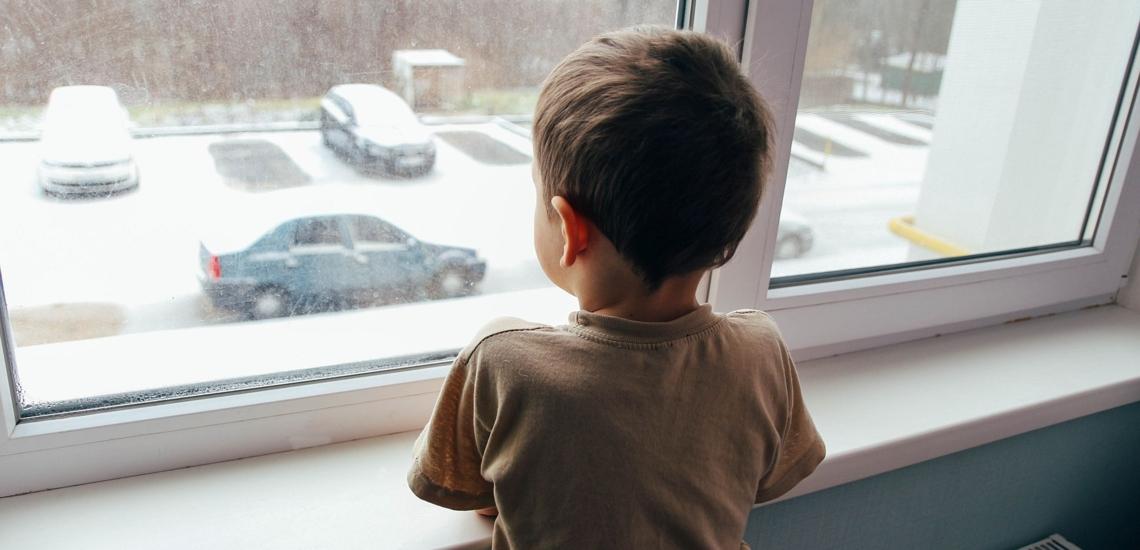 Junge sieht aus dem Fenster