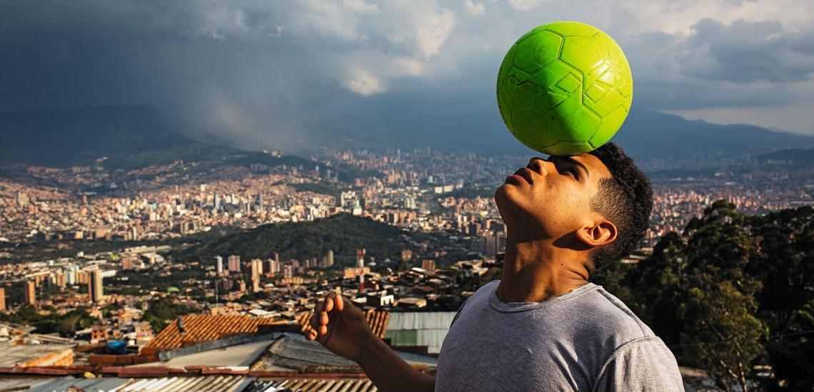 Junge mit Fußball vor Stadtkulisse von Medellin