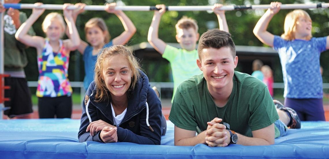 Zwei Jugendliche liegen auf Sportmatte und lachen in die Kamera