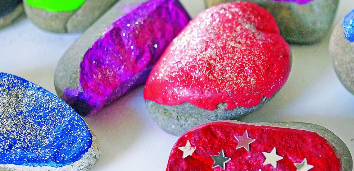 Mit Farben und Glitzer verzierte Steine