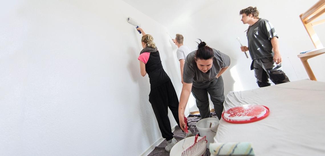 Jugendliche streichen im Don Bosco Jugendwerk Nürnberg ein Zimmer mit weißer Farbe