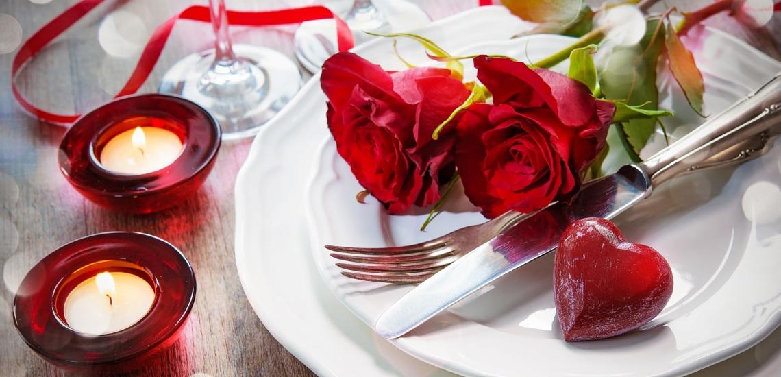 Tischdekoration mit Kerzen, roten Rosen und Herz