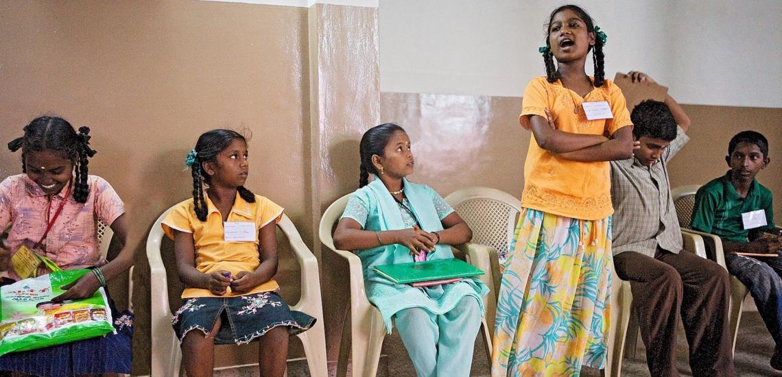 Kinder auf Stühlen, ein Mädchen steht und spricht