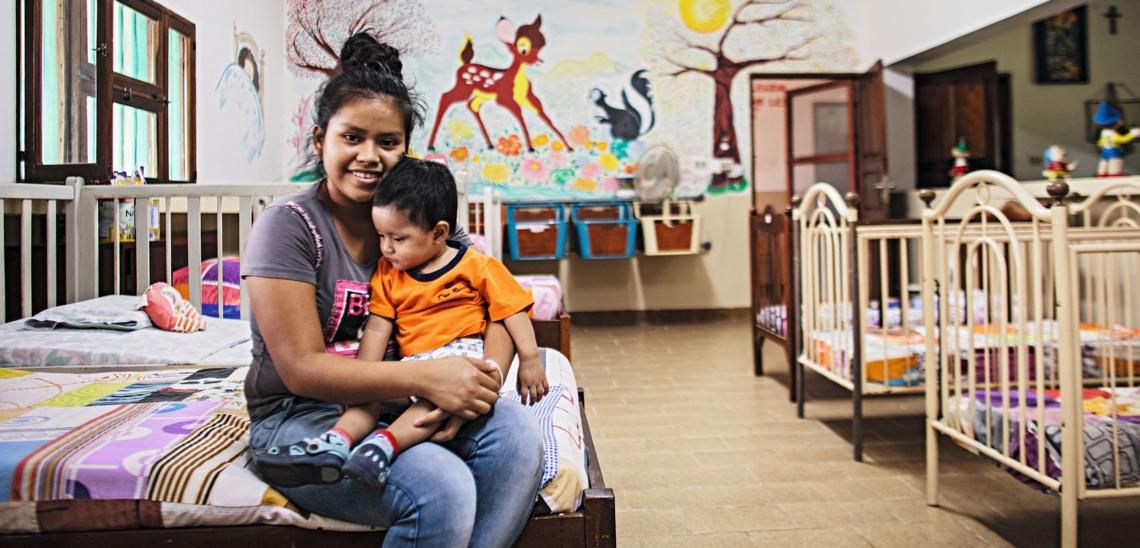 Junge Mutter mit Kind in freundlichem Schlafsaal mit vielen Betten