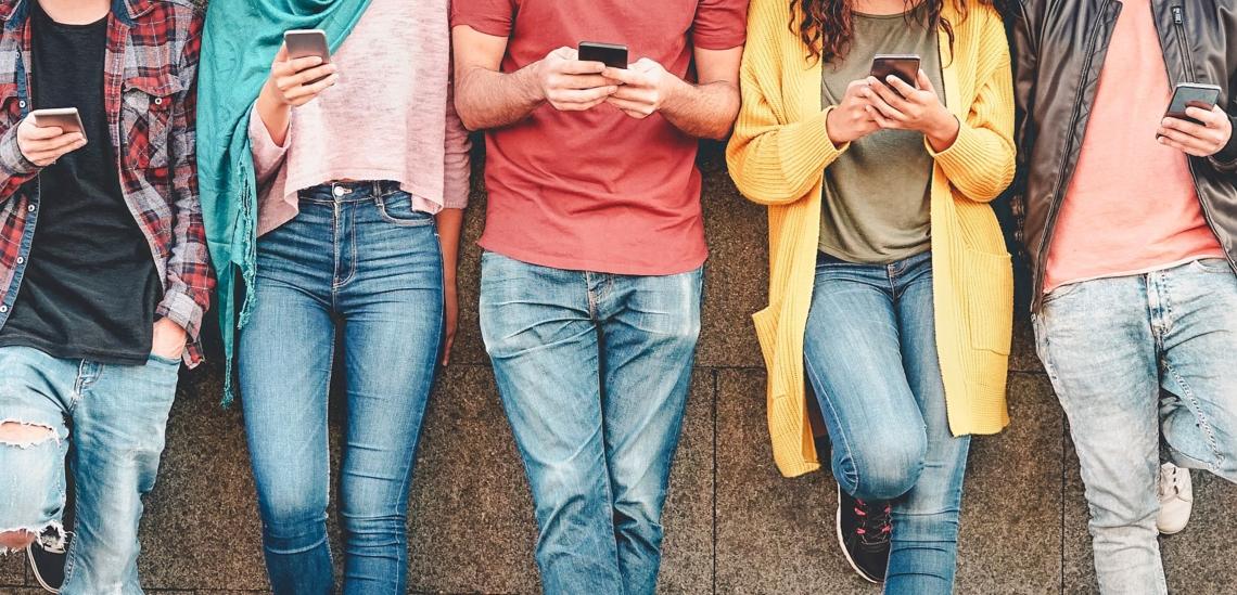 Jugendliche in einer Reihe mit Handy in der Hand
