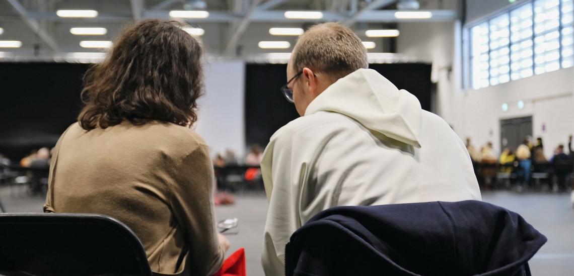 Rückenansicht Beichtende mit Priester bei Gespräch in Kongresshalle