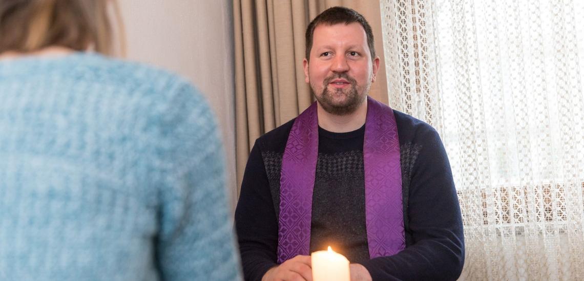 Beichtgespräch zwischen Pfarrer und Frau an Tisch mit Kerze