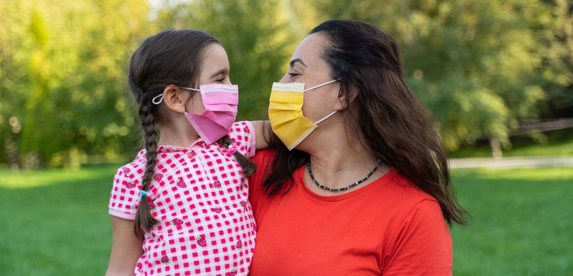 Mutter und Tochter lachend mit Masken auf Wiese