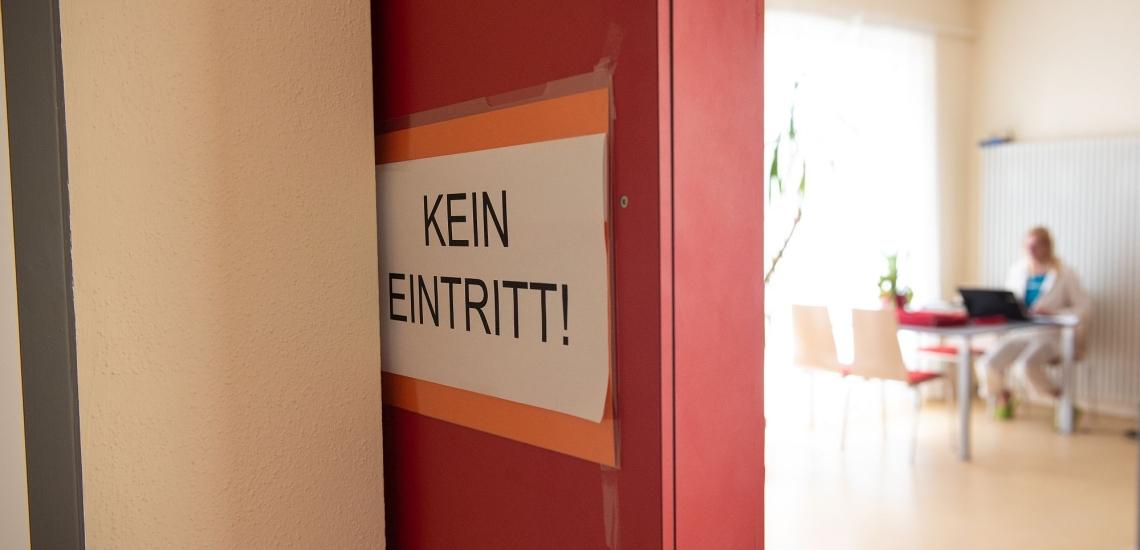 Schild Kein Eintritt! dahinter Raum mit Frau am Schreibtisch
