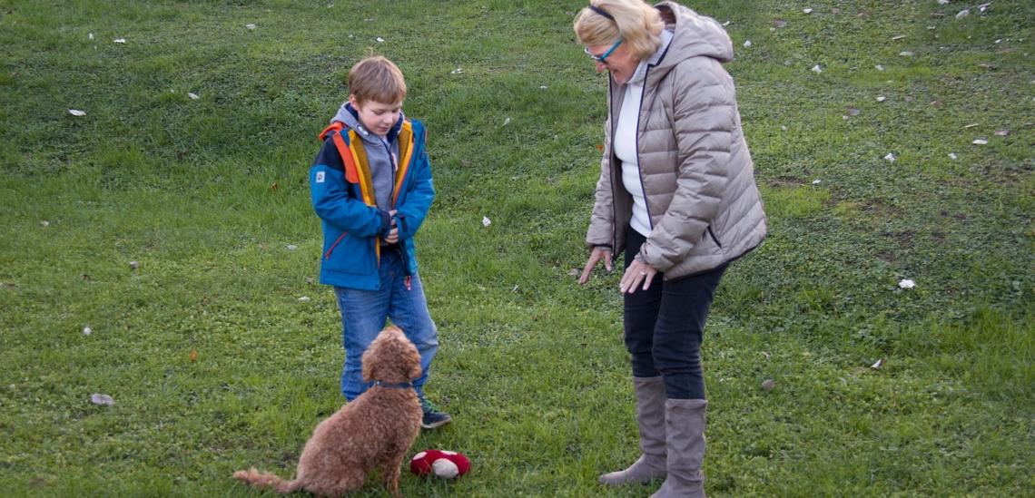Junge mit Seniorin und Hund auf Wiese