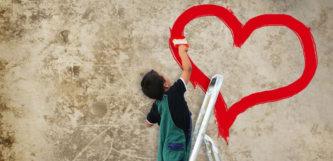 Kind malt mit roter Farbe Herz an die Wand