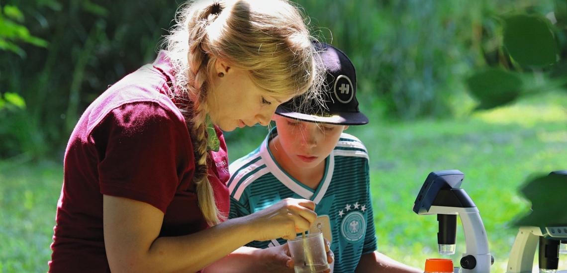 Junge Frau mit Junge an Mikroskop