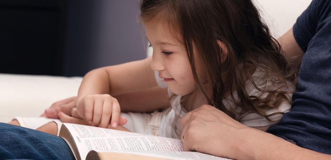 Mädchen liest mit Vater in Bibel