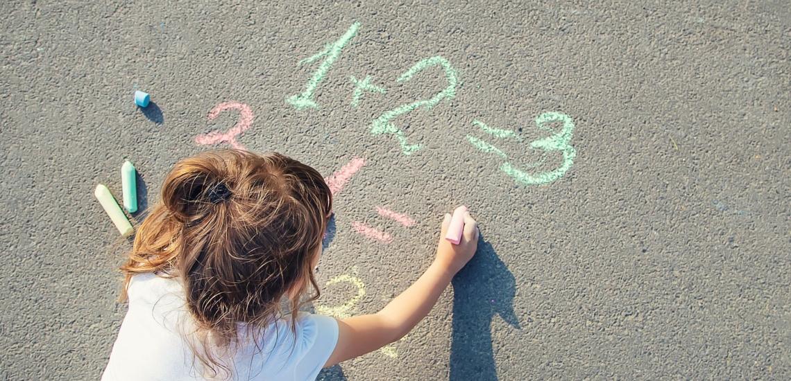 Mädchen schreibt mit Kreide Rechenaufgaben auf Straße