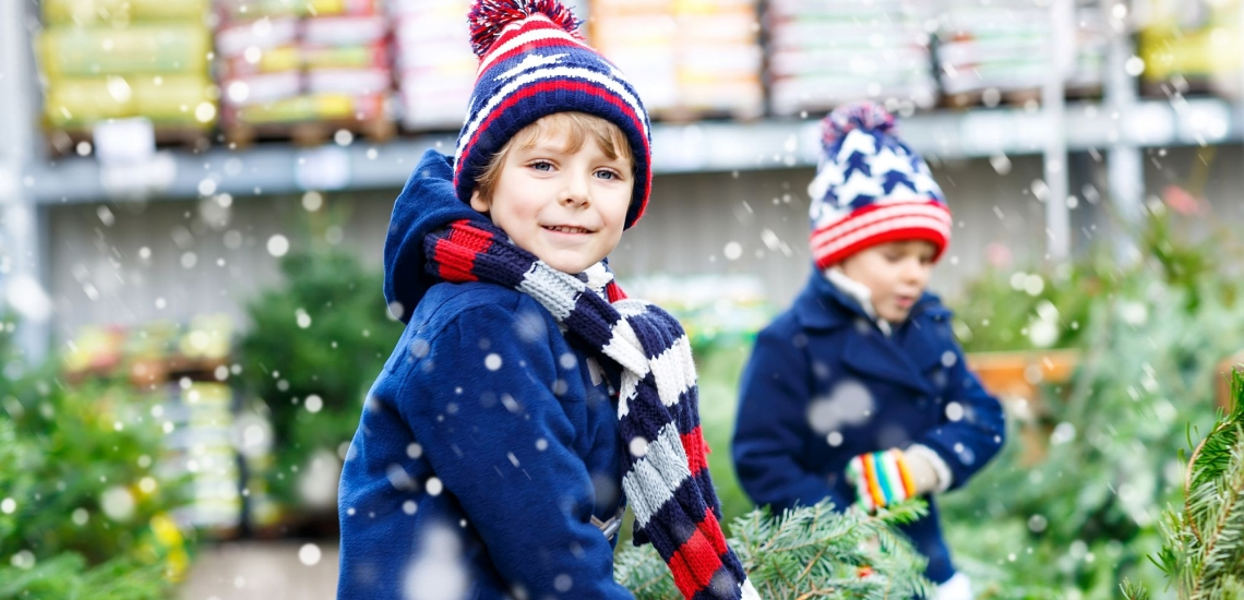 Zwei Jungen mit Tannenbäumen auf Markt