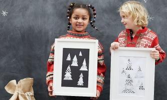 Zwei Kinder zeigen gerahmte Bilder