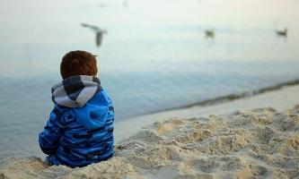 Kind sitzt einsam an Strand