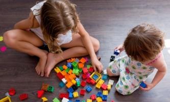 Zwei Schwestern spielen mit Legosteinen