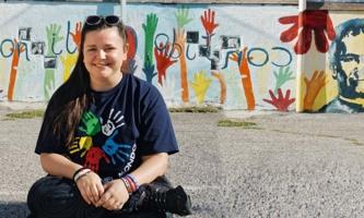 Junge Frau vor bunt bemalter Wand